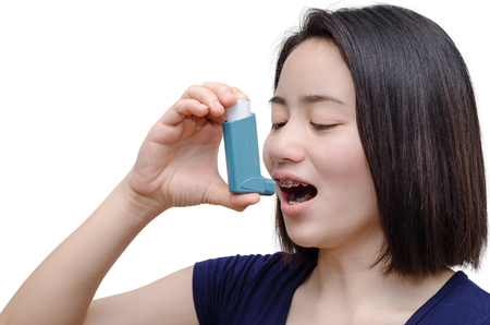 Young asian woman using inhaler over white background