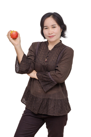aged: Middle aged asian woman holding an apple over white