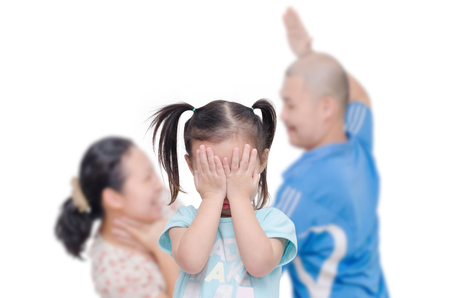 dysfunctional: Little asian girl crying between her parent fighting in background Stock Photo