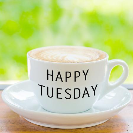 自然な背景の上のコーヒー カップに幸せな火曜日