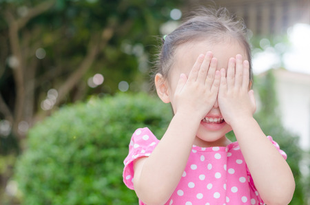 hide and seek: Little asian girl enjoy playing hide and seek outdoor Stock Photo