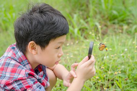 El muchacho asiático joven que usa la lupa para observar la mariposa en el jardín