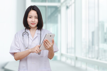 Beautiful asian doctor using tablet computer in hospital