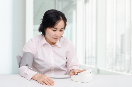 Asian woman checking blood pressure by herself