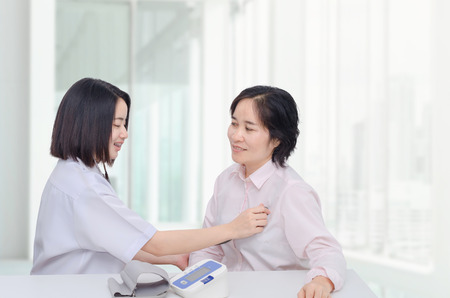 Asian doctor checking patient heart by stethoscope Stock Photo