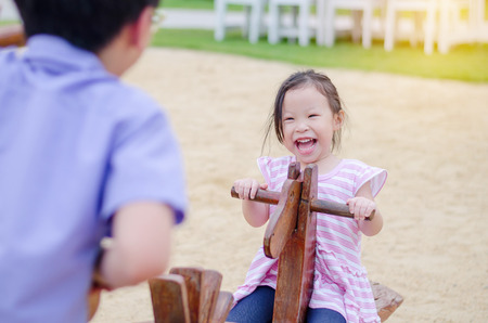 Little asian girl playing totter at playground