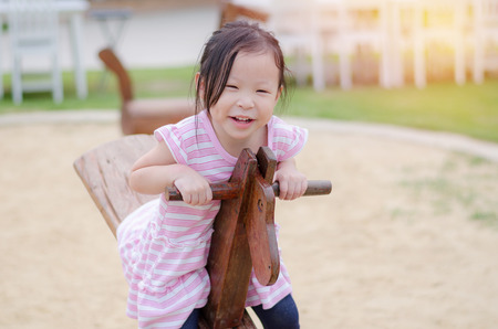 totter: Little asian girl playing totter at playground
