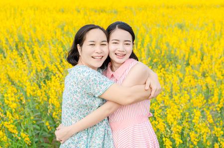 mère asiatique et sa fille au champ de fleurs Banque d'images