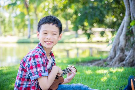 Young asian boy playing ukulele in park Stock Photo
