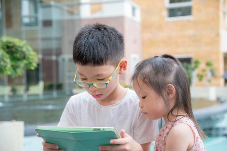 siblings: Asian siblings using a tablet computer Stock Photo