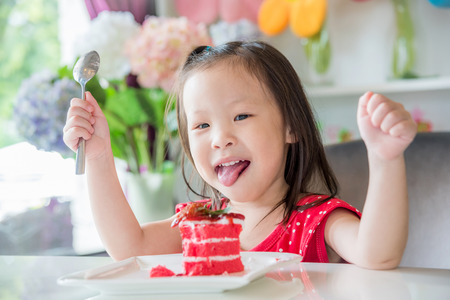 Little asian girl eating strawberry cake at home