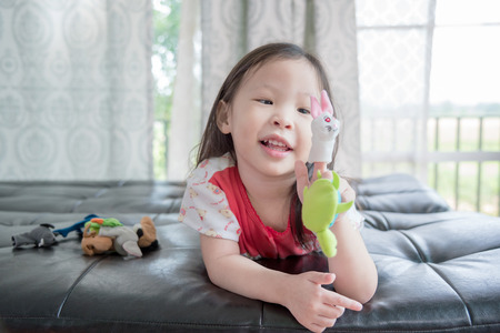 puppets: Little asian girl playing with animal puppets on sofa