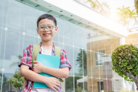 niños saliendo de la escuela: estudiante asiático sonriente en la escuela Foto de archivo