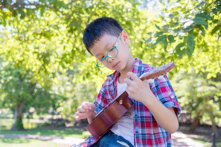 Young boy playing ukulele in park Stock Photo