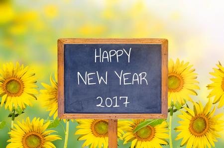 Happy New Year 2017 on blackboard with sunflower background