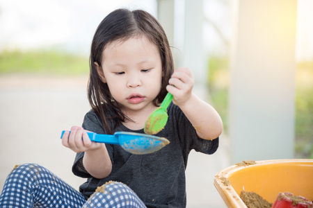 sandbox: Little asian girl playing sand in sandbox