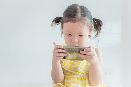asian family: girl playing games on smart phone Stock Photo
