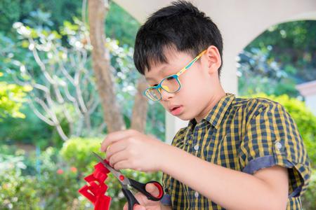 soustředění: Chlapec řezání papíru Reklamní fotografie