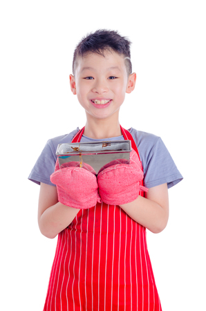 Young asian boy holding cake in tin over white Stock Photo