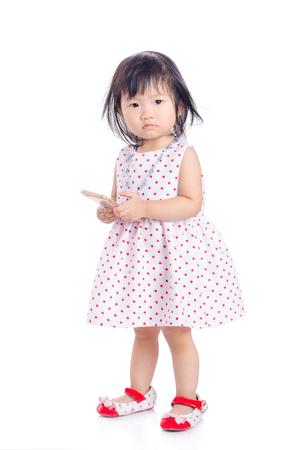 Little asian girl standing over white