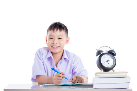 young asian schoolboy doing homework over white