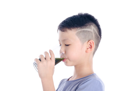 asian boy drinking vegetable juice photo