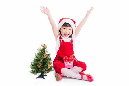 Little asian girl in santa dress sitting over white background Stock Photo