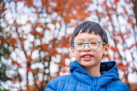 Asian boy smiling in autumn park Stock Photo