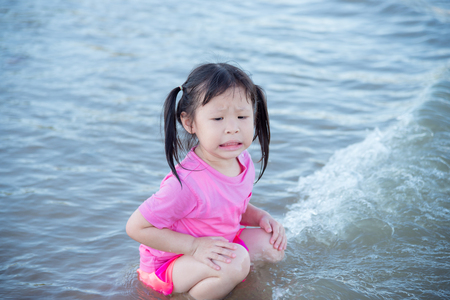 Little asian girl sitting on beach Stock Photo