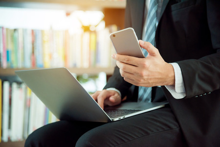 Hands of a businessman using mobile phone and laptop computer Stock Photo