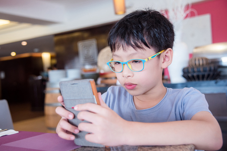 Young boy playing games on mobile phone Stock Photo