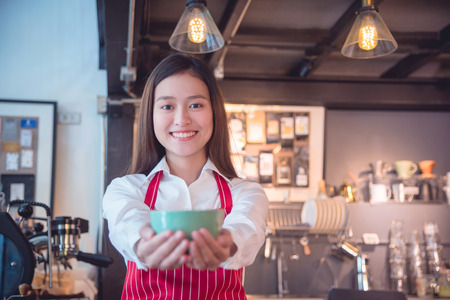 Beautiful asian barista holding coffee cup and smiles