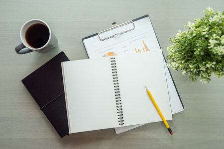 Notebook and coffee cup on table Stock Photo