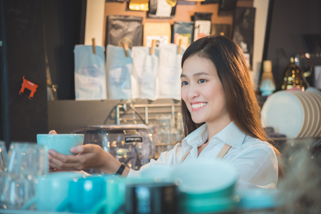 Beautiful barista holding coffee cup and smiles Stock Photo
