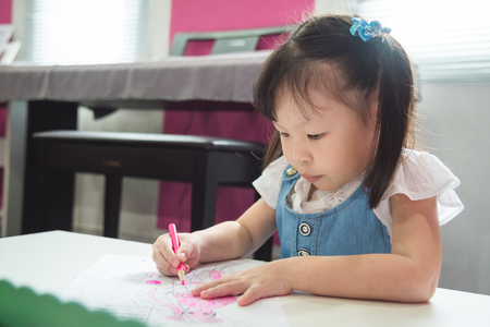 Little asian girl drawing picture at school