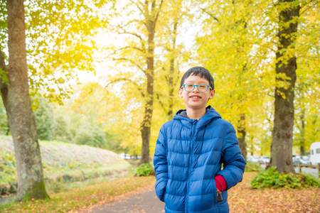 Young boy smiling in autumn park Stock Photo