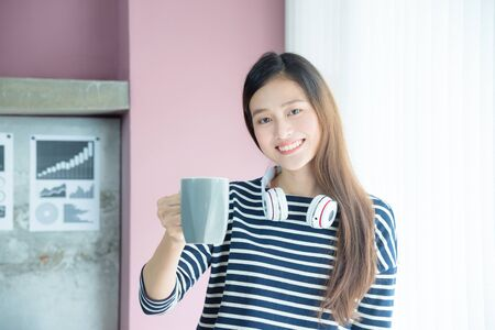 Beautiful woman holding coffee cup and smiles Stock Photo