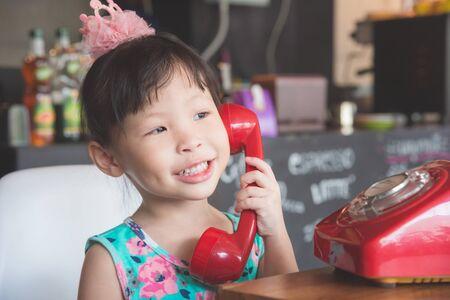 Little asian girl using telephone