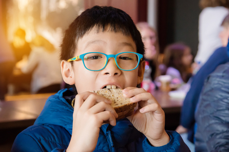 Young boy eating sanwich