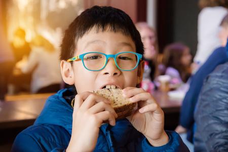 sanwich: Young boy eating sanwich