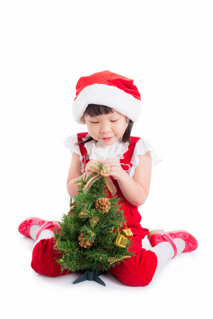 Little asian girl decorating christmas tree