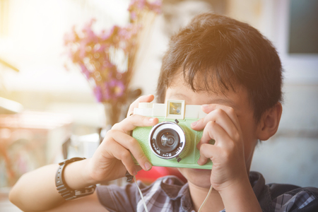 Boy taking photo by camera with vintage filter Stock Photo