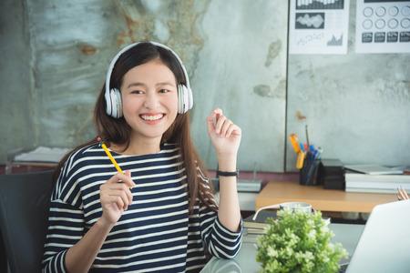 Beautiful asian woman listening music from headset
