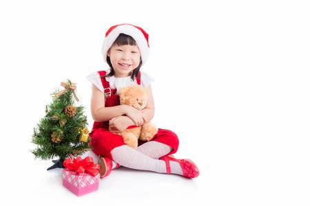 Little asian girl in santa dress sitting over white