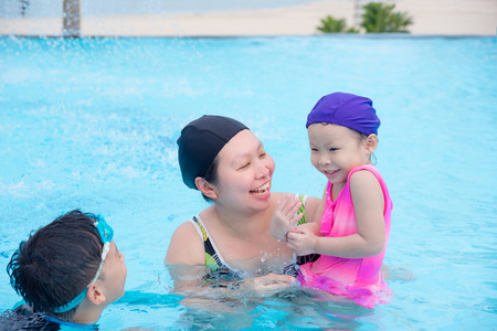 Mother and children in swimming pool Stock Photo