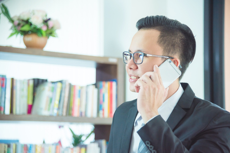 asian businessman talking with someone by mobile phone Stock Photo