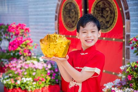 Chinese boy holding golden money bank