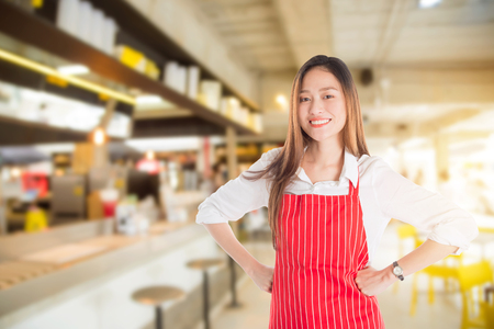 Beautiful restaurant owner smiling in front of her shop