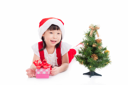 Little girl in santa dress with christmas tree Stock Photo