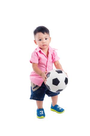 Little boy holding ball over white